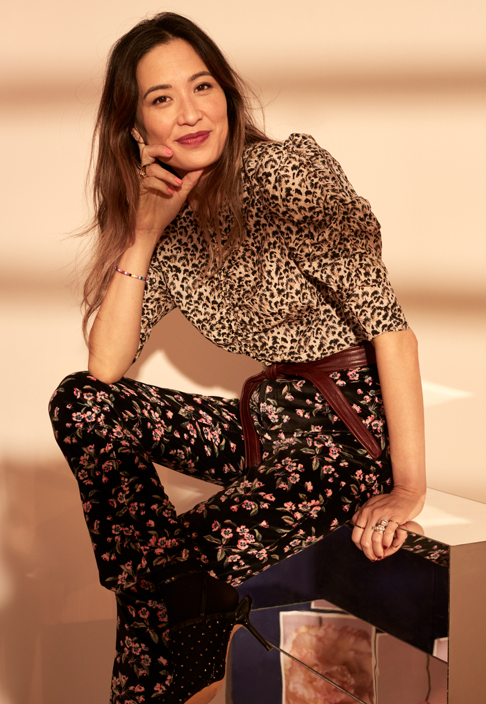 Caroline in leopard print top and floral pants sitting